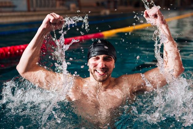 Glücklicher männlicher schwimmer des hohen winkels des sieges