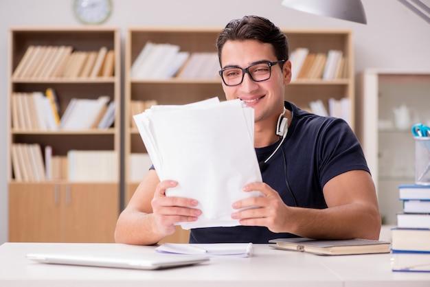 Glücklicher männlicher student, der für seine prüfungen sich vorbereitet