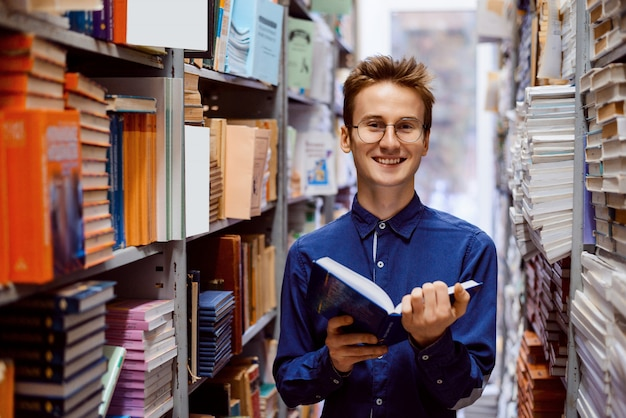Glücklicher männlicher student, der in bibliothek mit buch steht
