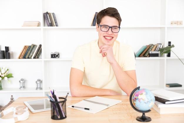 Glücklicher männlicher student, der mit leerem notizbuch sitzt