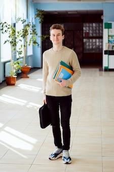 Glücklicher männlicher student mit büchern und einem laptop im korridor der universität