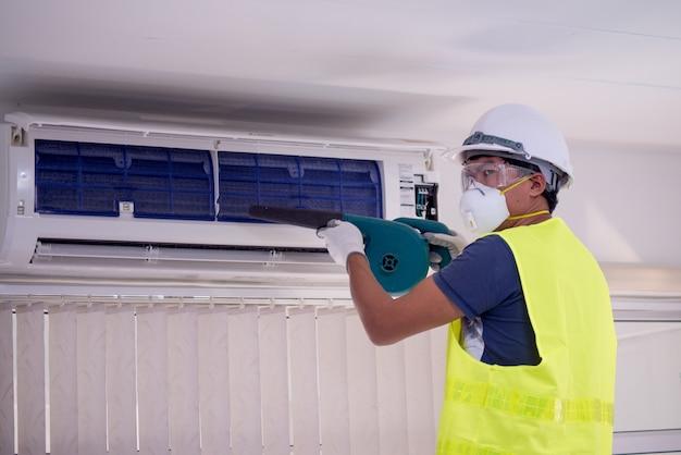 Glücklicher männlicher techniker repairing air conditioner mit sicherheitshut und -luft