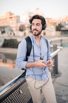 Glücklicher männlicher tourist, der auf dem geländer hört musik sich lehnt