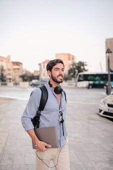 Glücklicher männlicher tourist mit dem laptop, der auf pflasterung geht