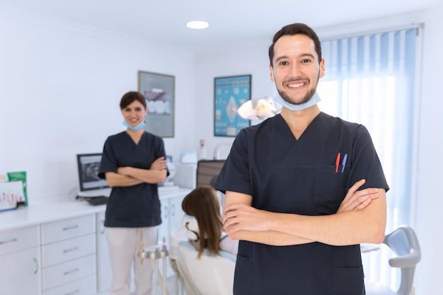 Glücklicher männlicher und weiblicher zahnarzt in der zahnmedizinischen klinik