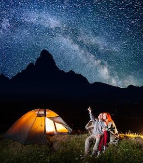 Glücklicher männlicher wanderer, der rothaarige dame an den sternen und an der milchstraße im himmel zeigt. paare, die nahe dem beleuchtungszelt sitzen