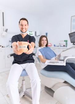 Glücklicher männlicher zahnarzt, der das zahnmodell sitzt vor weiblichem patienten an der zahnmedizinischen klinik zeigt