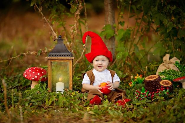 Glücklicher märchenhafter babygnomjunge, der im wald spielt und geht, pilze pflückt, äpfel isst