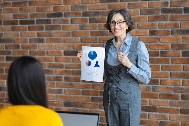 Glücklicher manager im büro zeigt umsatzbericht mit positivem wachstum