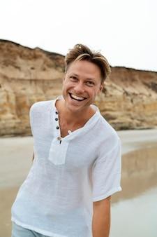 Glücklicher mann am strand mittlerer schuss