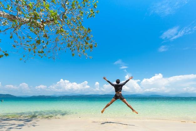 Glücklicher mann am weißen sandstrand und am boot des langen schwanzes in insel khang khao (schlägerinsel), die schöne meer-ranong-provinz, thailand.
