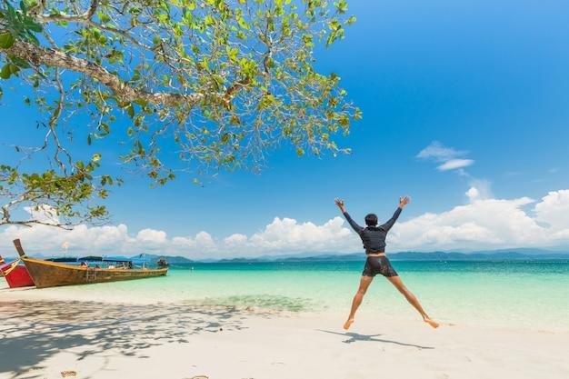 Glücklicher mann am weißen sandstrand und am boot des langen schwanzes in khang khao island (schlägerinsel), die schöne see ranong-provinz, thailand.