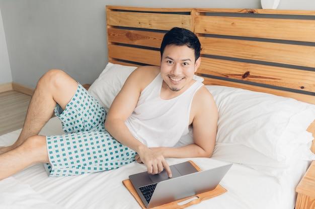 Glücklicher mann arbeitet mit seinem laptop auf seinem bett.
