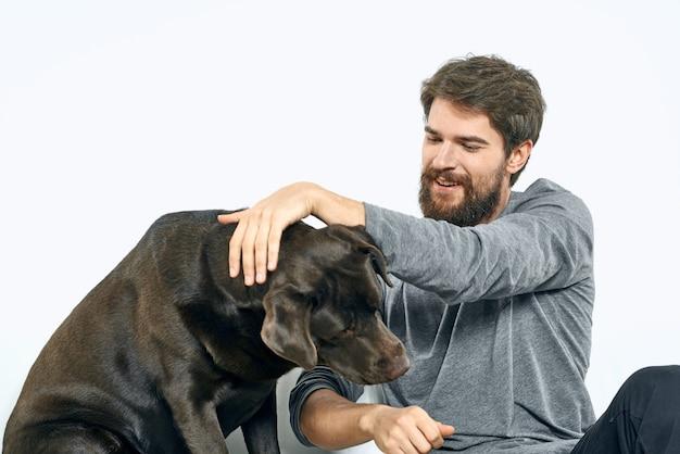 Glücklicher mann auf sofa mit seinem hund, isolation und quarantäne mit hund zu hause