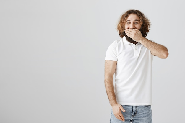 Glücklicher mann aus dem nahen osten bedeckt den mund und lacht