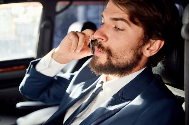 Glücklicher mann, der am telefon im nahaufnahmeanzug des autoporträts spricht