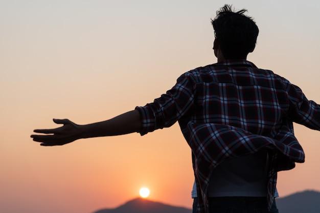 Glücklicher mann, der arme ausbreitet und den berg beobachtet