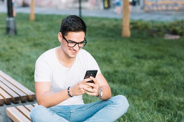 Glücklicher mann, der auf bank unter verwendung des mobiltelefons sitzt