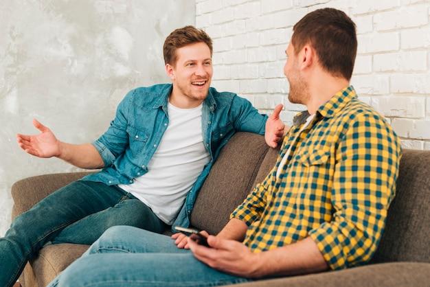 Glücklicher mann, der auf dem sofa in der hand spricht mit seinem freund hält mobile sitzt