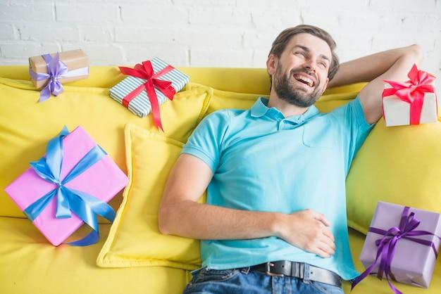 Glücklicher mann, der auf dem sofa umgeben durch verschiedene geburtstagsgeschenke sich entspannt