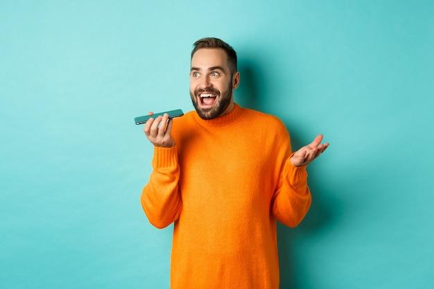 Glücklicher mann, der auf freisprecheinrichtung spricht, gestikuliert und sprachnachricht auf mobiltelefon aufzeichnet, im orange pullover über hellblauem hintergrund stehend.