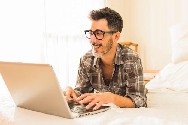Glücklicher mann, der auf gemütlichem bett unter verwendung des laptops liegt