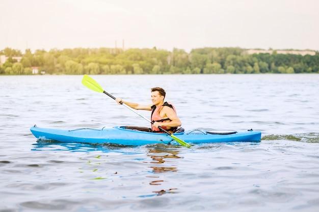 Glücklicher mann, der auf geplätschertem wasser kayaking ist