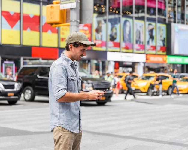 Glücklicher mann, der auf seinem smartphone simst