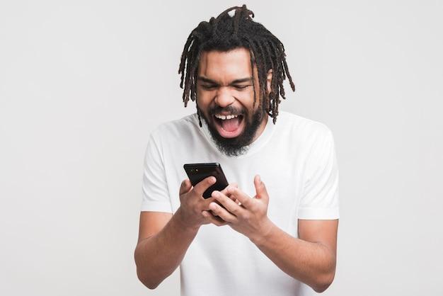 Glücklicher mann, der auf smartphone schaut