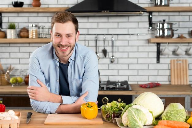 Glücklicher mann, der auf tabelle mit frischer vielzahl des gemüses in der inländischen küche sich lehnt