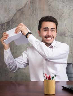 Glücklicher mann, der bündel von papieren am schreibtisch hält.