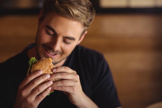 Glücklicher mann, der burger isst