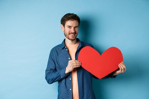 Glücklicher mann, der das herz des valentinsgrußes zeigt und lächelt, machen romantisches geschenk am liebhabertag, das über blauem hintergrund steht.
