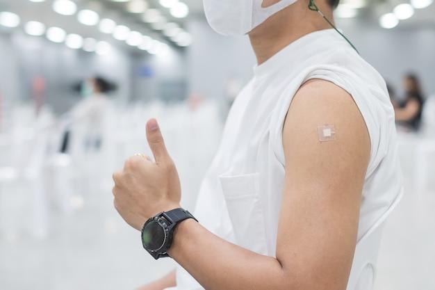 Glücklicher mann, der daumen zeigt, nachdem er impfstoff erhalten hat. impfung, impfung, impfung und coronavirus (covid-19) pandemie