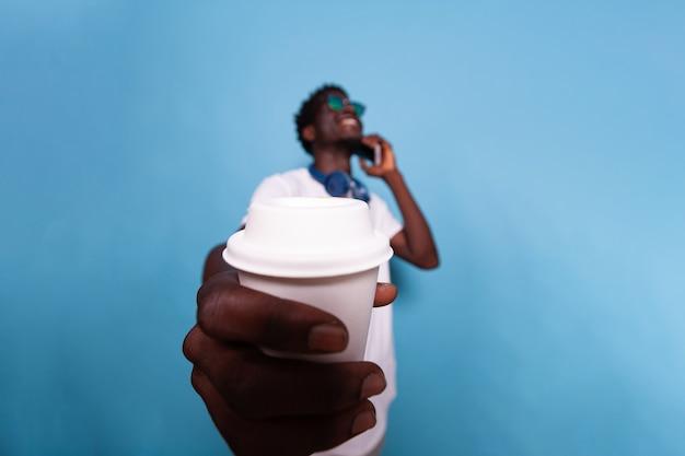 Glücklicher mann, der der kamera eine tasse kaffee zeigt