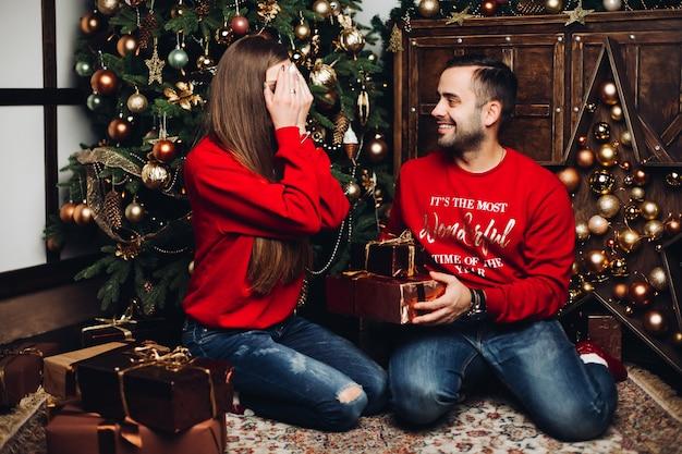 Glücklicher mann, der die augen seiner freundin am weihnachten bedeckt
