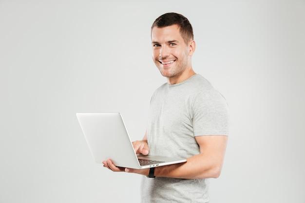 Glücklicher mann, der durch laptop-computer plaudert.