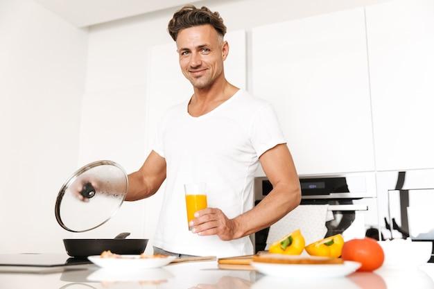 Glücklicher mann, der eier zum frühstück kocht