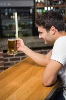 Glücklicher mann, der ein bier trinkt
