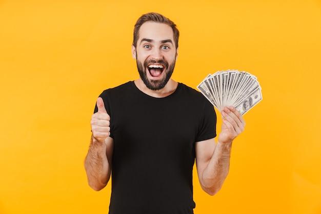 Glücklicher mann, der ein einfaches schwarzes t-shirt trägt und lächelt und geld bargeld isoliert über gelber wand hält?