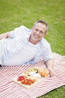 Glücklicher mann, der ein picknick draußen hat