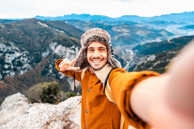 Glücklicher mann, der ein selfie nimmt berge
