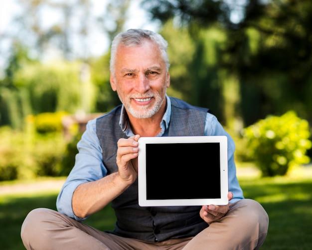 Glücklicher mann, der ein tablettenmodell hält