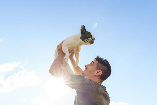 Glücklicher mann, der eine bulldogge hält. horizontale ansicht des mannes mit haustier im freien. lebensstil mit tieren