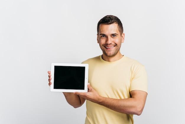 Glücklicher mann, der eine tablette im handmodell hält