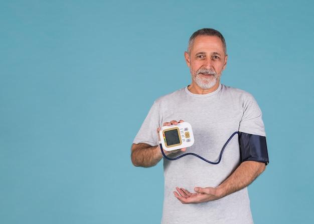 Glücklicher mann, der ergebnisse des blutdrucks auf elektrischem tonometer zeigt
