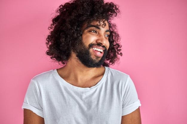 Glücklicher mann, der fröhlich lächelnd im studio mit rosa hintergrund, arabischer positiver kerl aufwirft