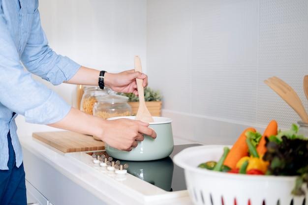Glücklicher mann, der gesundes essen in der dachbodenküche zu hause kocht