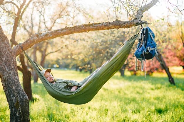 Glücklicher mann, der im sommerpark in der hängematte schläft.