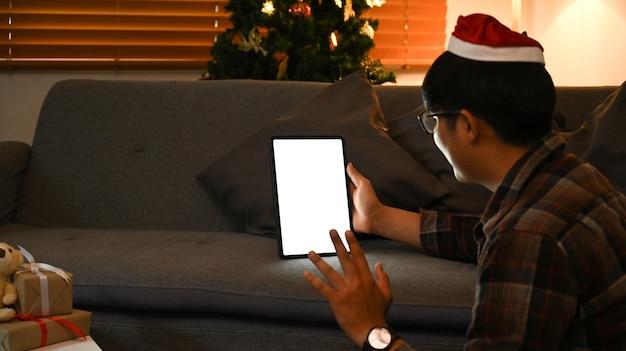 Glücklicher mann, der im wohnzimmer und videoanruf mit digitalem tablet sitzt.